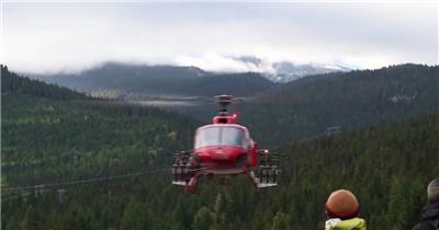 人们观看红色直升飞机起步飞行到深山处直升飞机飞行高清视频实拍