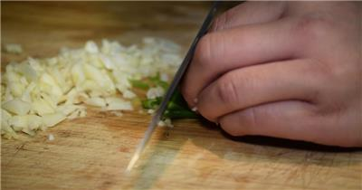 厨师切蒜头成蒜粒葱为葱花熟手快速巧手切开工作高清视频拍摄