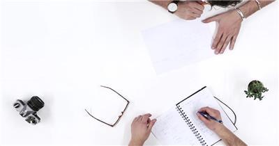 办公桌相机小植物商讨设计事宜写写画画人物工作高清视频实拍