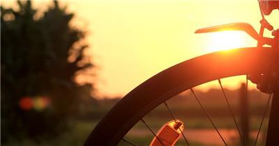 夕阳黄昏照射自行车车轮变焦光点自行车宣传高清视频实拍