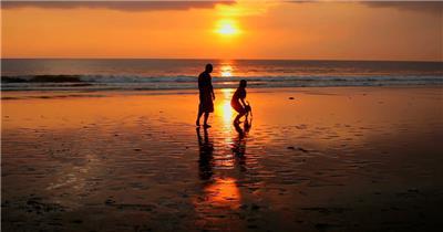 在夕阳下遛狗玩耍的恋人素材         coupleplayingonbeachwithdogatsunsetinbali 视频素材下载