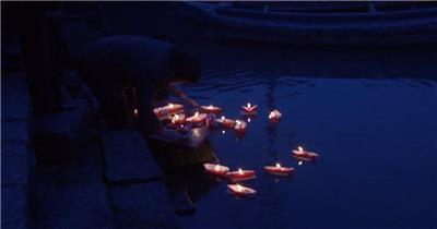 蜡烛纸船燃点祝福之光海岸边投放纸船河流上飘荡高清视频实拍